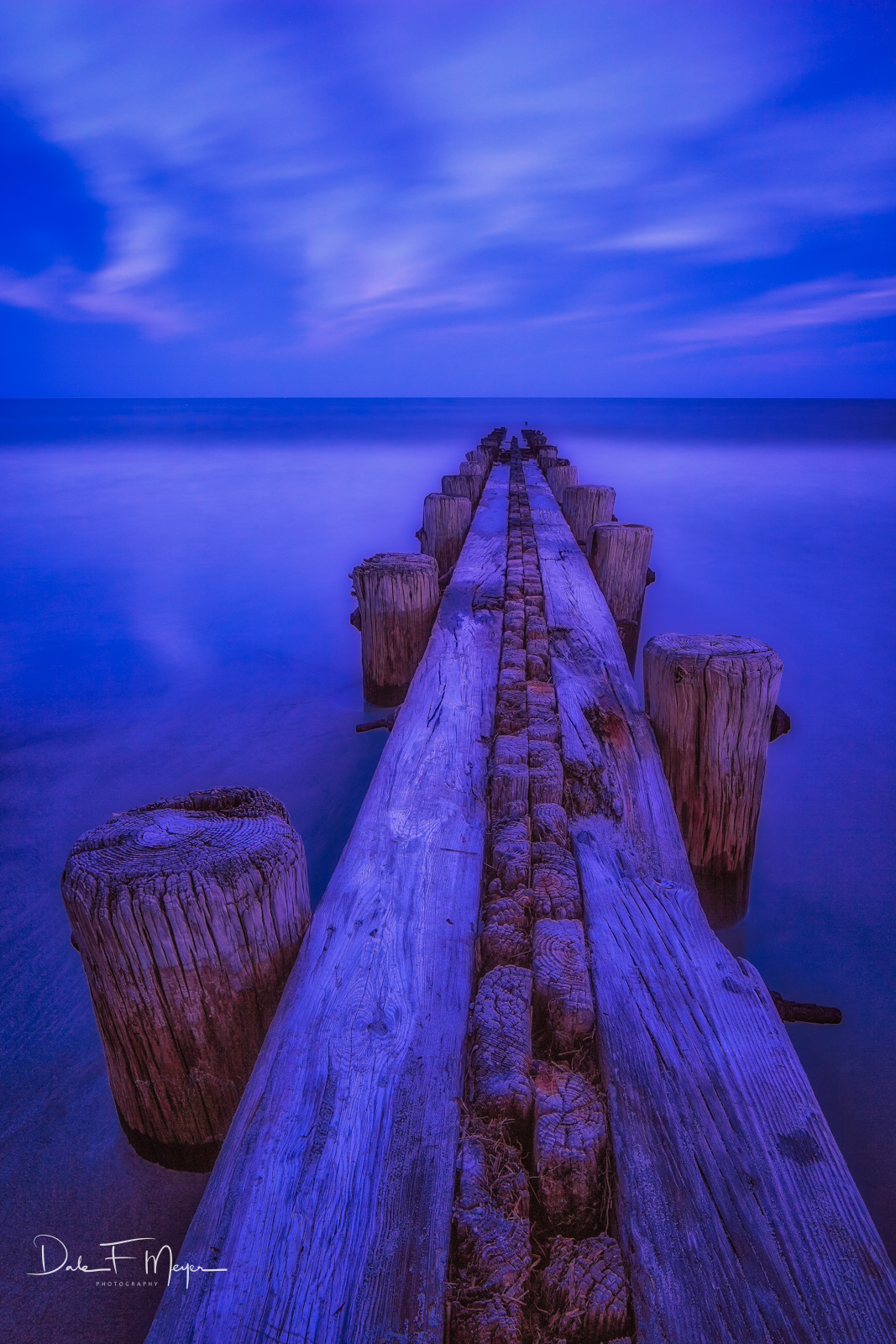 Ocean Jetty shot in the blue hour with a setting sun from behind illuminating the warm colors in the old worn wood. This was...